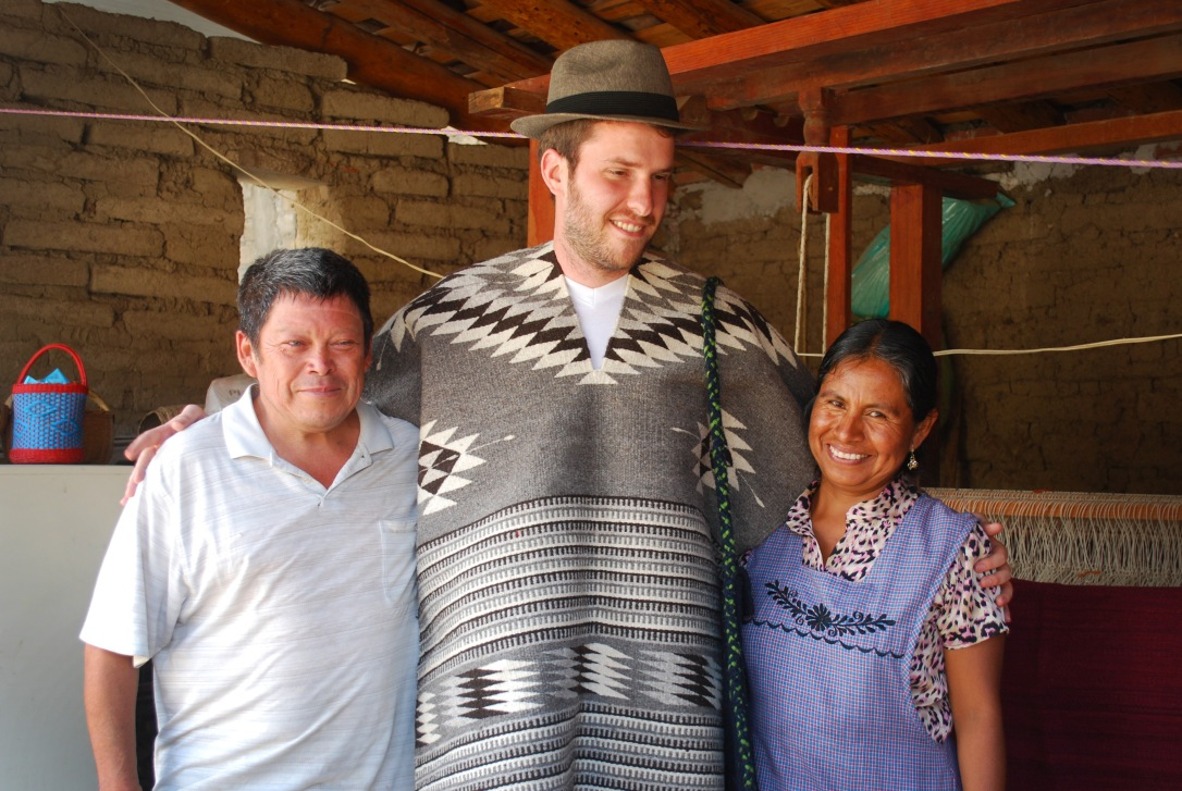 Fundación En Vía borrower Soledad Martinez Sanchez (right),  her husband (left) and volunteer translator Bryce Bray (center) who is wearing products produced with her interest-free loan.