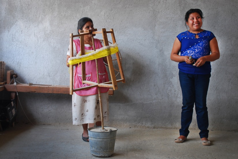 Gabriela (right) and her mother Rosa (left) explain the spinning process of wool to our En Via responsible tourism group.