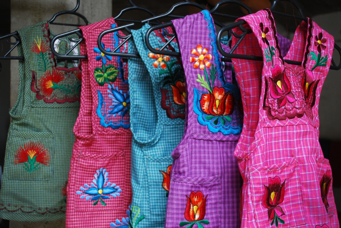 A selection of aprons for little girls, sewn and embroidered by hand by Martha.