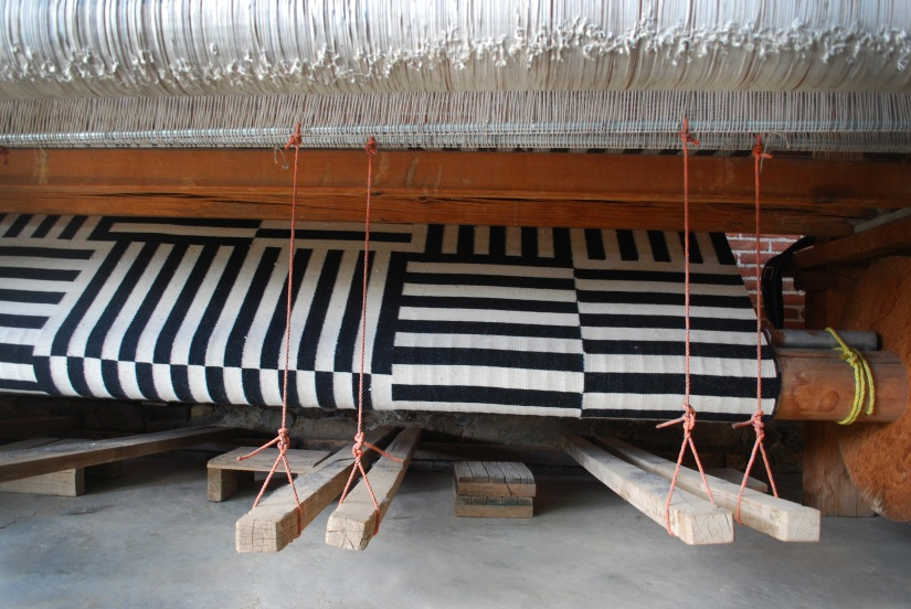 A geometric pattern is prepared on a standing pedal loom for an international client.