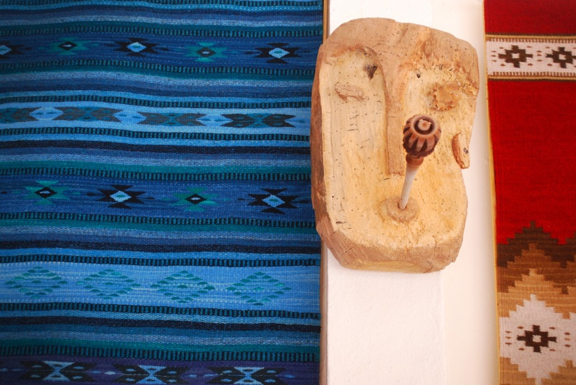 A sampling of two hand-woven tapetes and a wood sculpture.