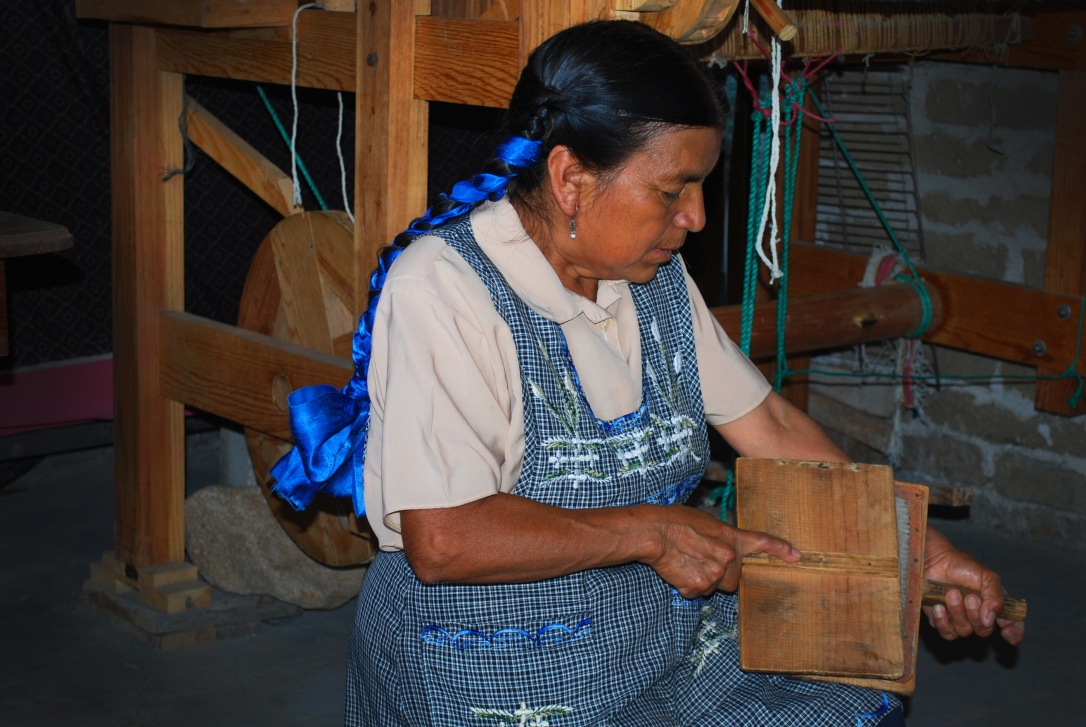Eulalia demonstrates the process of carding raw wool by hand.