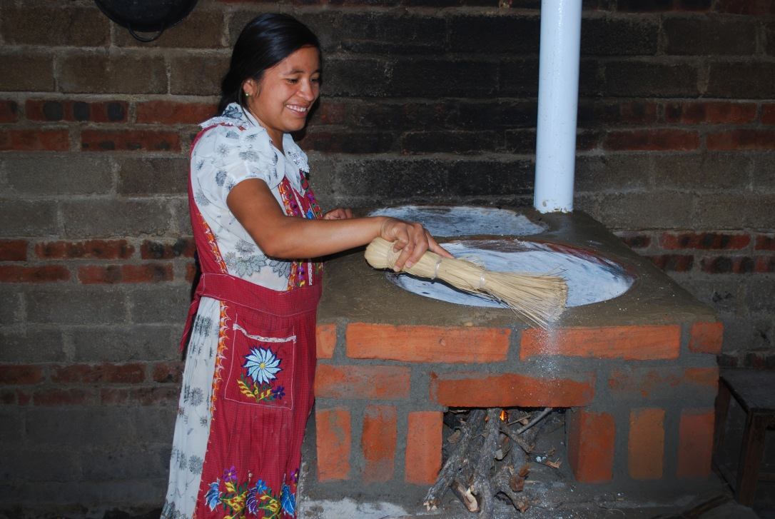 A borrower prepares her newly built stove after the completion of a community build.