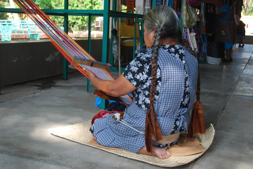 An artisan works with cotton and a backstrap loom in the local market.