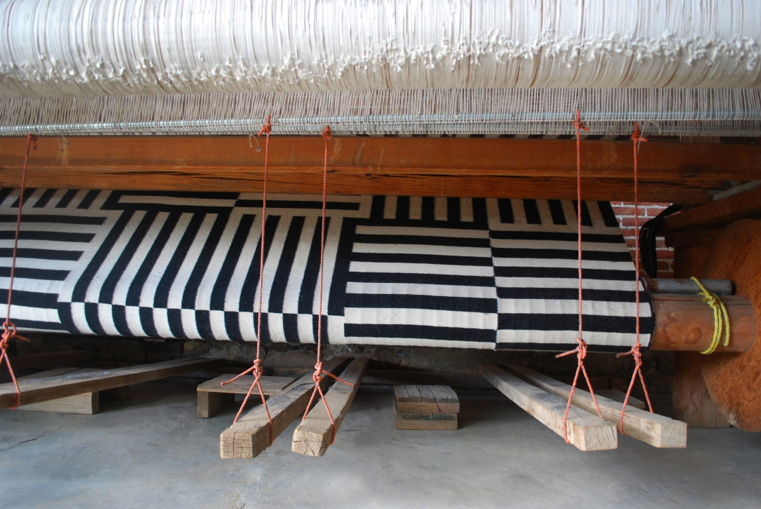 Amazing custom rug on the standing foot pedal loom of a borrower family workshop.