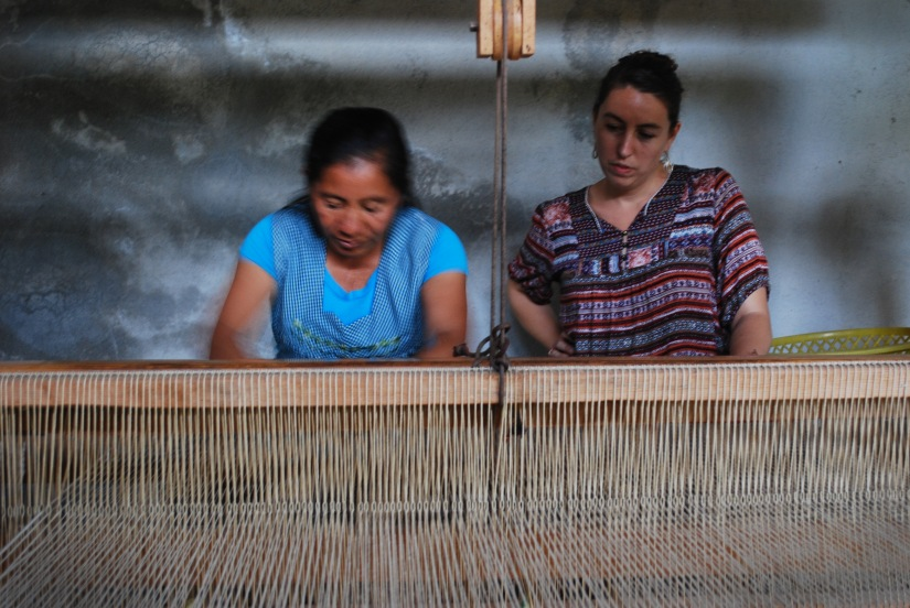 Mica Miro, Responsible Tourism Program Manager for Fundacion En Via, looks on as a textile artisan explains her process.
