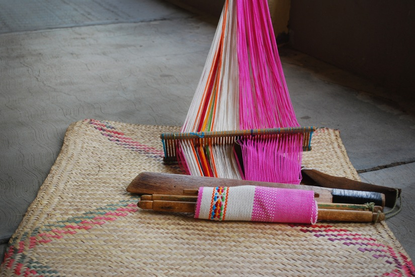 A brightly colored textile piece waits as an artisan takes a short break to stretch her legs.