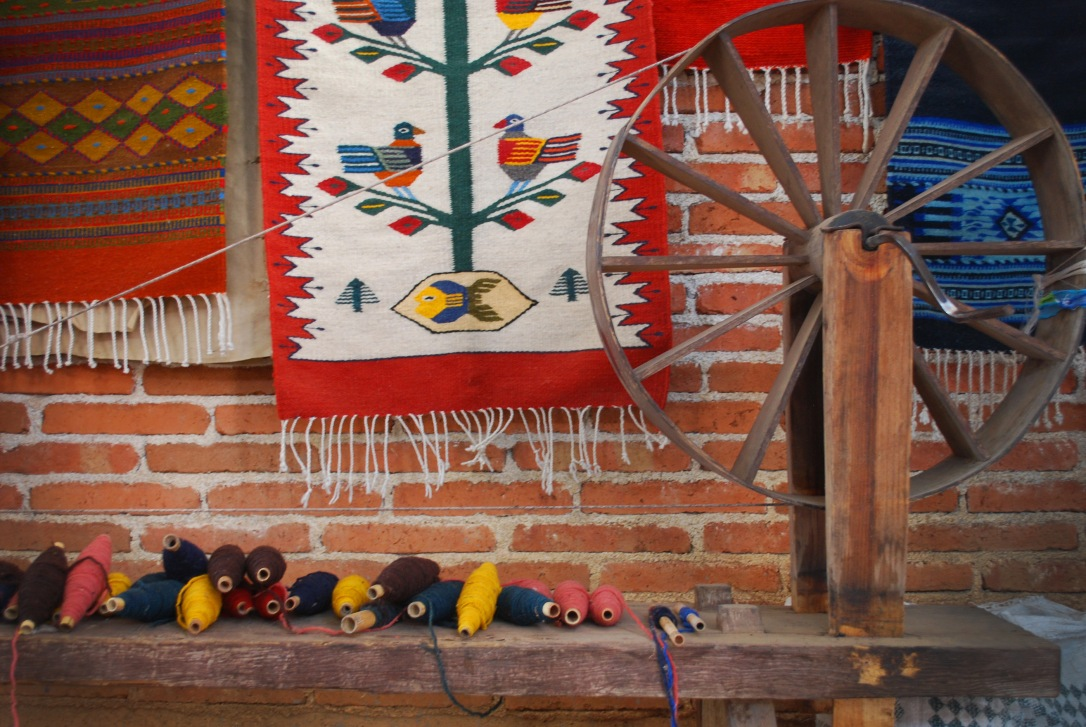 A spinning wheel is arranged with colored wool and a selection of handmade tapetes.