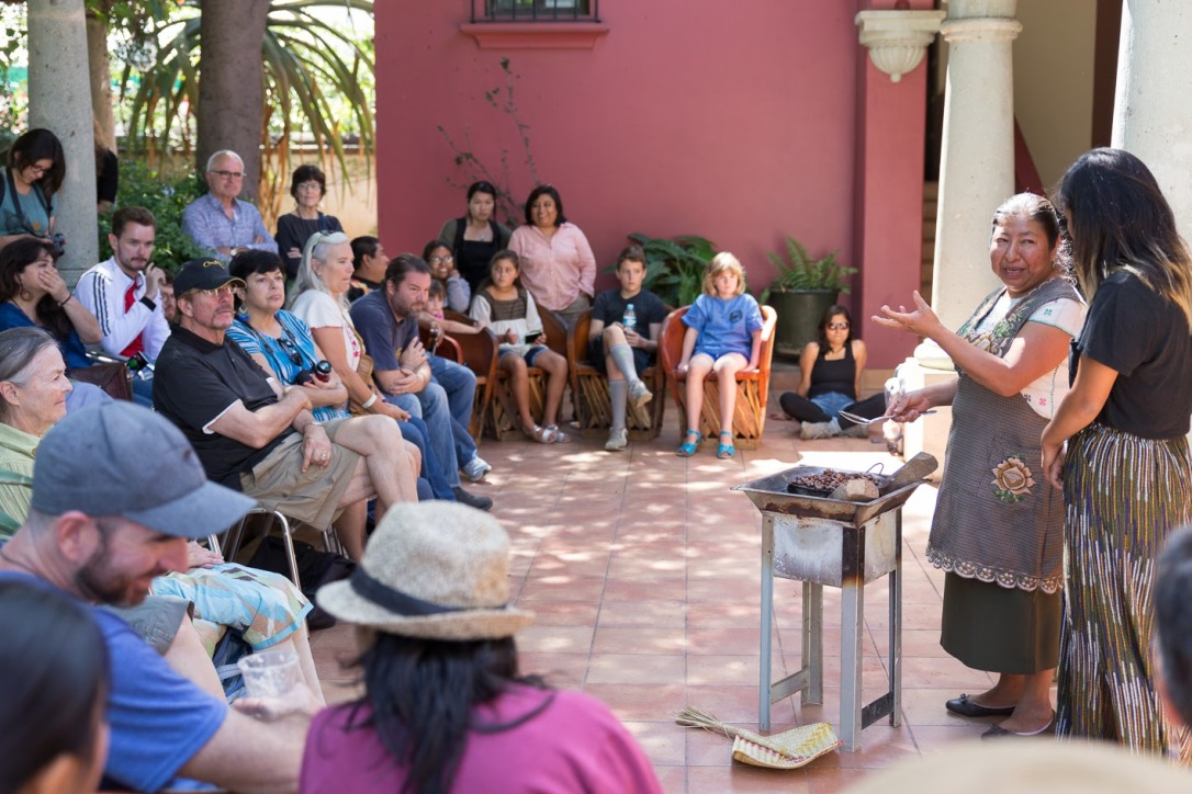 Isabel explains to Eda her process of making chocolate. Audience members listen closely.