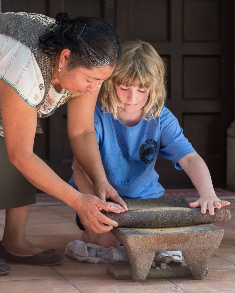 Isabel helps a young volunteer use the metate.