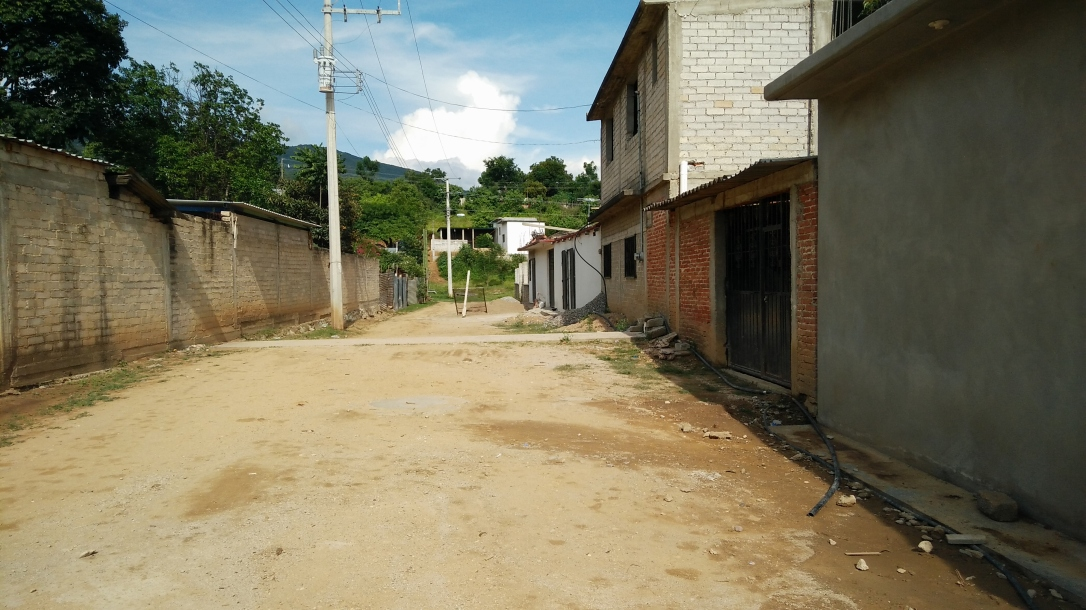 A view of an empty dirt road in Santo Domingo Tomaltepec in late afternoon.