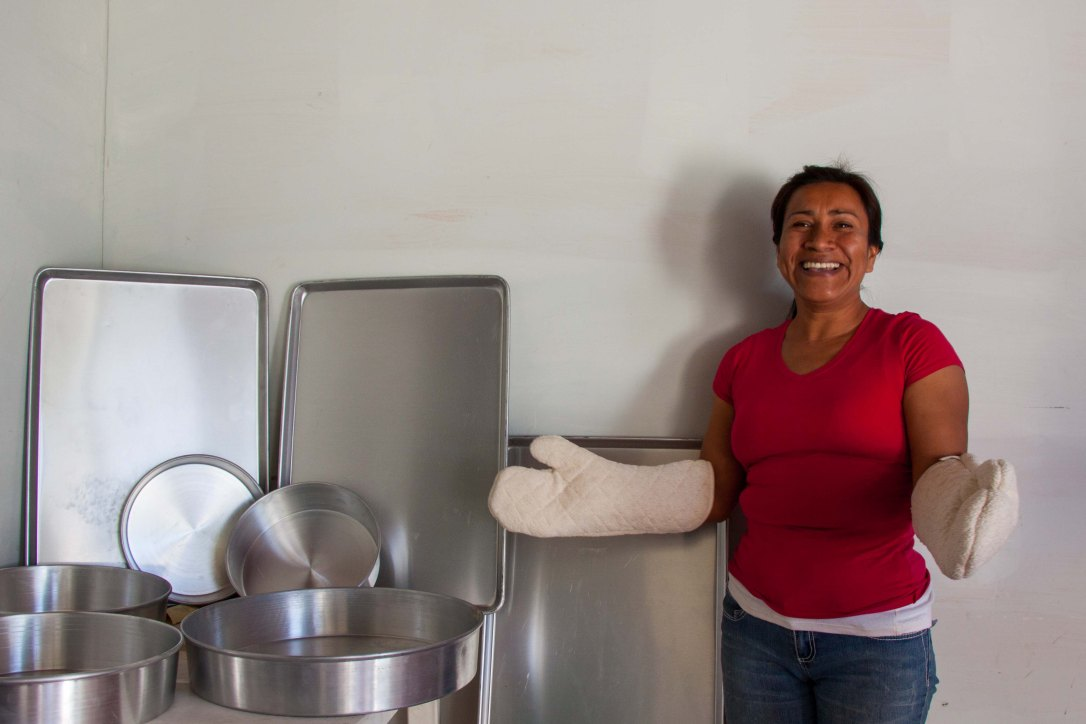 A woman with baking mittens on her hands smiles as she stands next to new baking pans and tins.