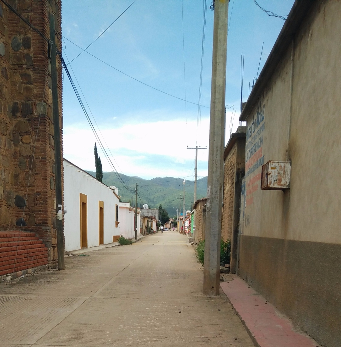 An empty road in a small pueblo with a blue sky and brown and white buildings. Wires connect the buildings.
