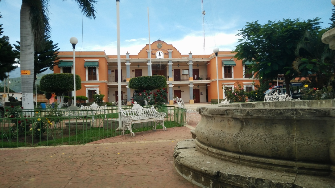 The municipio building of Santo Domingo Tomaltepec from the view of a courtyard with a fountain and a bench.