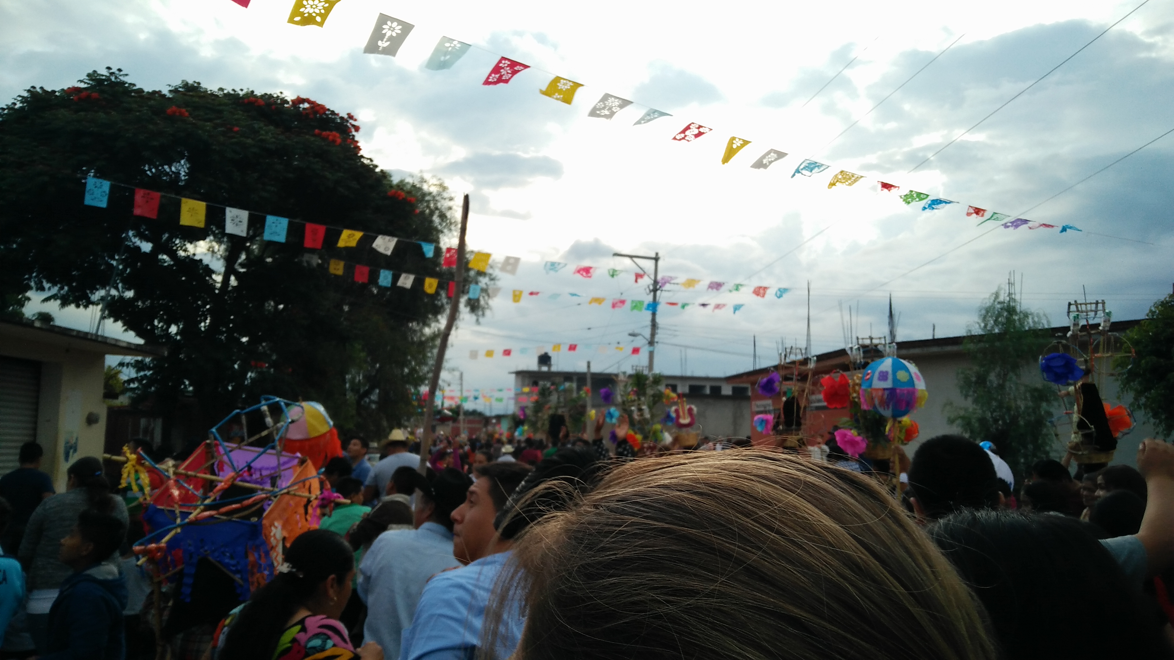 A large crowd of people walk through the streets of Tomaltepec. Papel picado cross the buildings of the city.