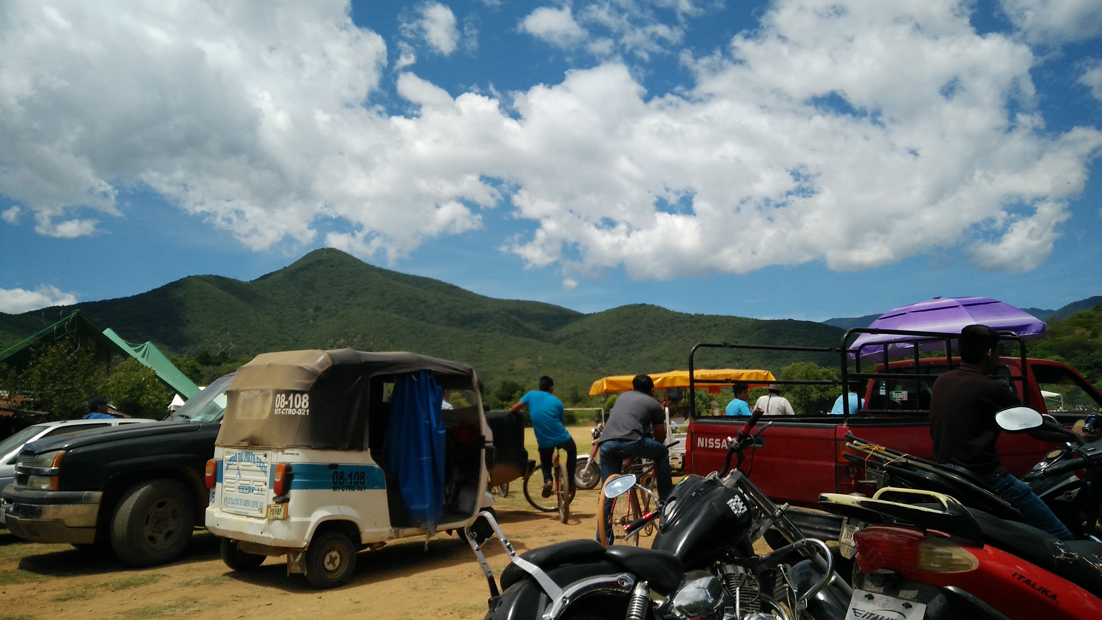 Motorcycles, two men, and cars are parked in a dirt field in front of mountains and a blue sky.